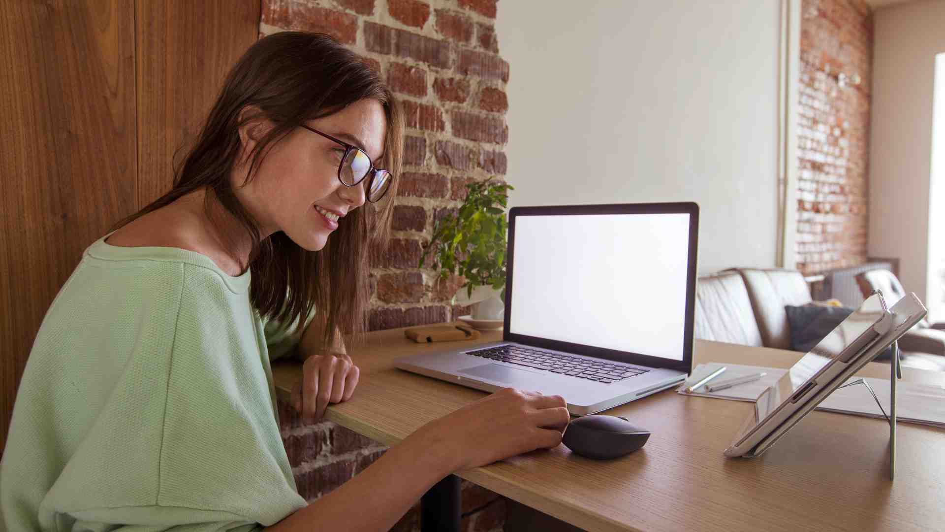 Side view of woman in glasses working at home using laptop and tablet while sitting at table in apartment with brick walls